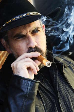 hombre fumando puro: Hombre con barba en el sombrero de vaquero fumar cigarro Foto de archivo