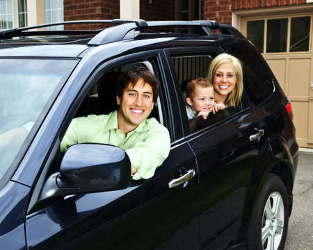 Happy young family sitting in black car looking out windows Standard-Bild