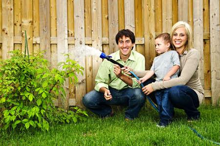 hose: Happy family en la planta de jard�n con manguera de riego