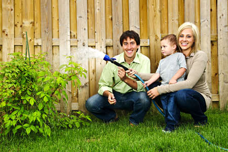 Happy family in backyard watering plant with hose Imagens