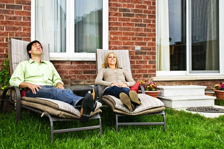 Happy couple in backyard of new home sitting on lounge chairs photo