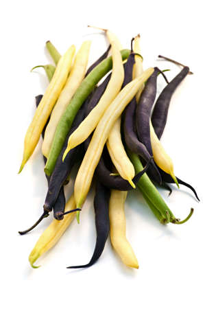 Pile of purple yellow and green string beans isolated on white