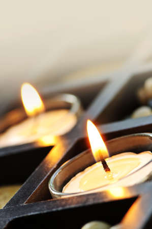 Burning candles in glass holders and wooden stand photo