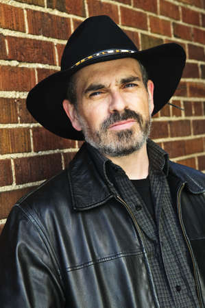 middle aged men: Man with beard in cowboy hat and leather jacket