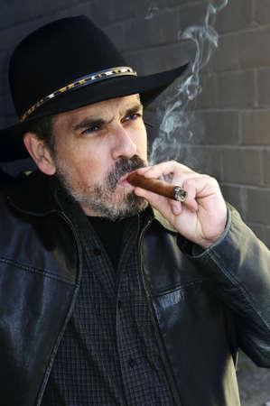 Man with beard in cowboy hat smoking cigar photo