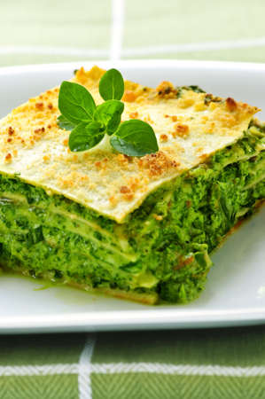 Serving of fresh baked vegeterian spinach lasagna on a plate photo