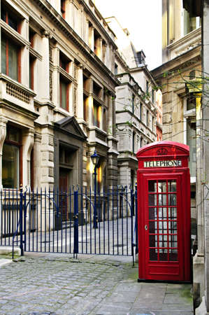 Red telephone box near old buildings in London photo