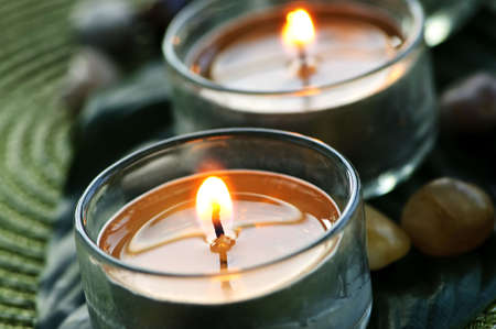 candle holder: Burning candles in glass holders on green leaf Stock Photo