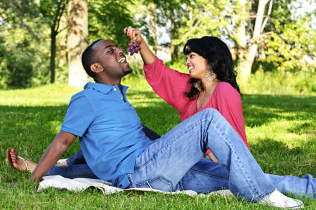 Young romantic couple having picnic in summer park photo