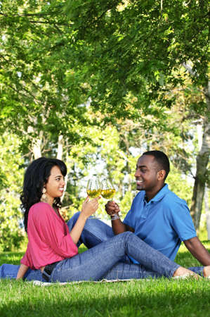 Young romantic couple celebrating with wine in summer park photo