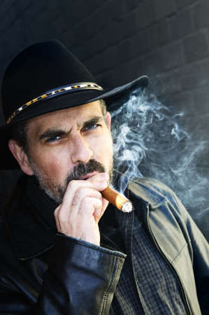 Man with beard in cowboy hat smoking cigar photo