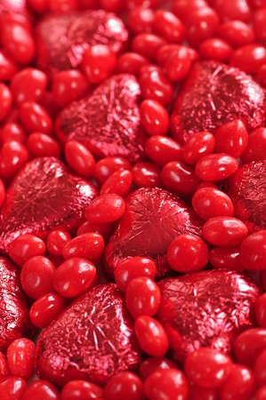foil: Background of red Valentines candies and foil wrapped chocolates Stock Photo