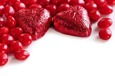 foil: Red Valentines candies and foil wrapped chocolates on white background Stock Photo