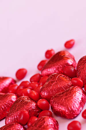 Red Valentine's candies and foil wrapped chocolates on pink background Stock Photo - 5601441
