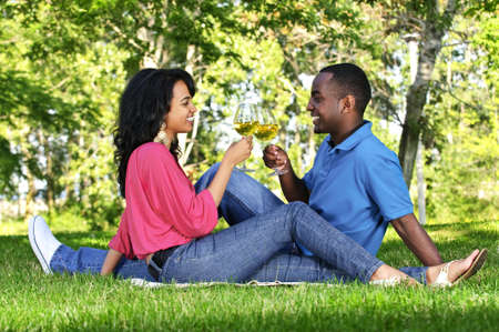 Young romantic couple celebrating with wine in summer park Фото со стока