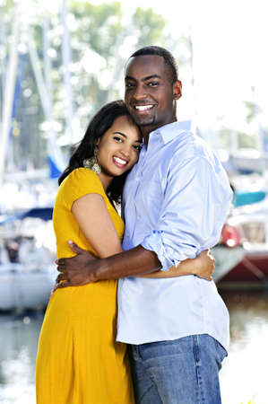 minority couple: Young romantic couple hugging and standing at harbor Stock Photo