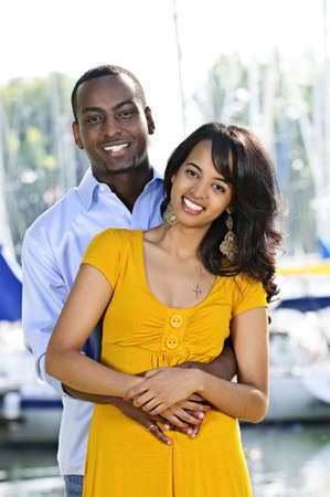 Young romantic couple hugging and standing at harbor Stock Photo