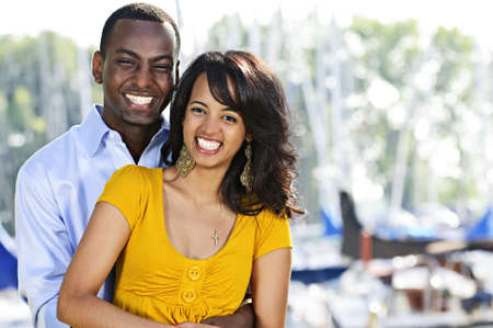 Young romantic couple hugging and standing at harbor photo