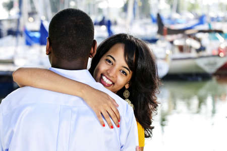 Beautiful young woman hugging boyfriend standing at harbor photo