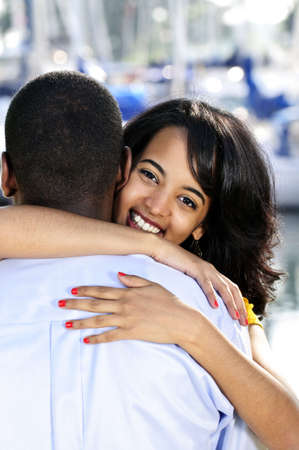 Portrait of beautiful young woman hugging boyfriend standing at harbor photo