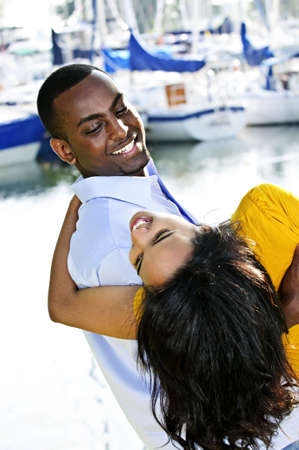 Portrait of man playfully carrying his girlfriend at harbor photo