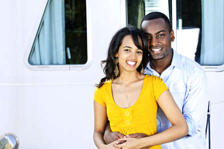 minority couple: Portrait of young romantic couple hugging in front of yacht