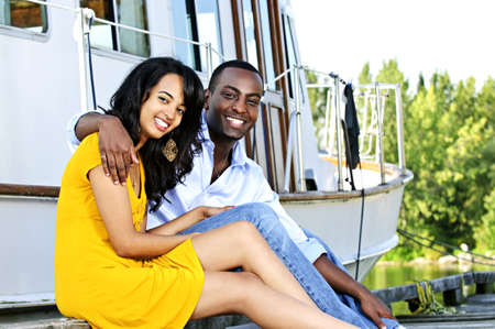 Young romantic couple sitting on dock in front of yacht Stock Photo