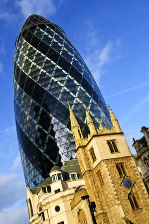 gherkin: Gherkin building contrasted with old gothic church of St. Andrew Undershaft in London England