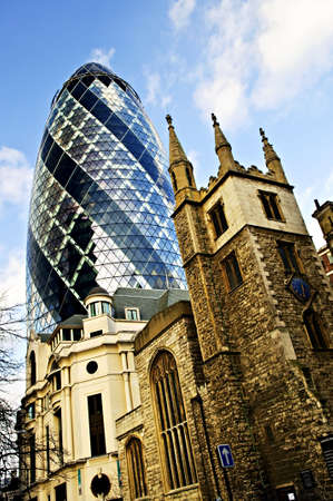 Gherkin building contrasted with old gothic church of St. Andrew Undershaft in London England