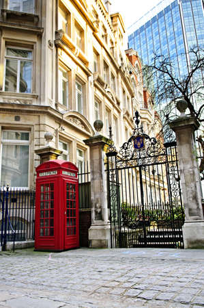 Red telephone box near old and new buildings in London photo