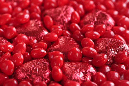 Background of red Valentines candies and foil wrapped chocolates Reklamní fotografie