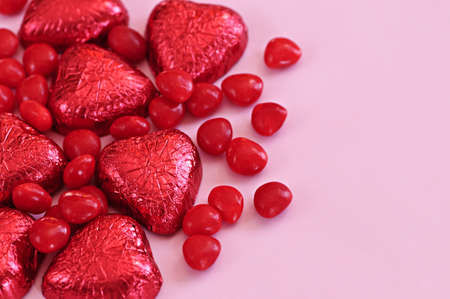 foil: Red Valentines candies and foil wrapped chocolates on pink background Stock Photo