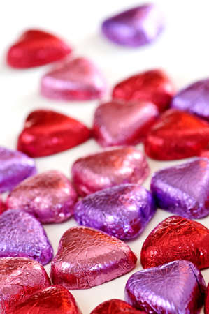 heart shaped: Valentines chocolates wrapped in red and purple foil on white background