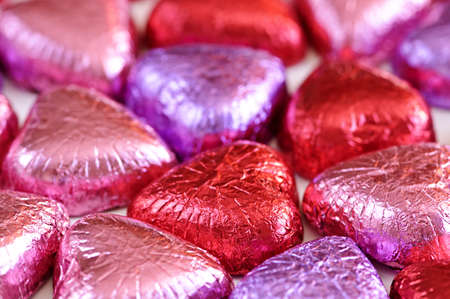 foil: Background of Valentines chocolates wrapped in red and purple foil