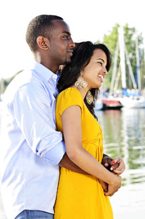 Young romantic couple hugging and standing at harbor in profile photo