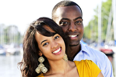 minority couple: Portrait of young romantic couple standing at harbor Stock Photo