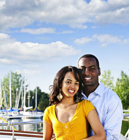 Portrait of young romantic couple standing at harbor with copyspace photo