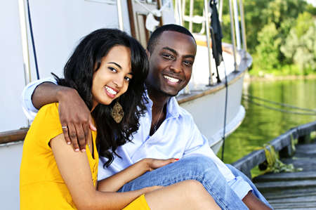 Young romantic couple sitting on dock in front of yacht photo