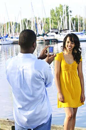 Beautiful woman posing for vacation photo at harbor with sailboats photo