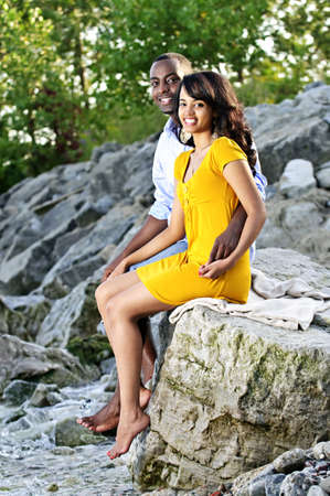Happy couple dipping feet in ocean sitting on boulder at rocky shore photo