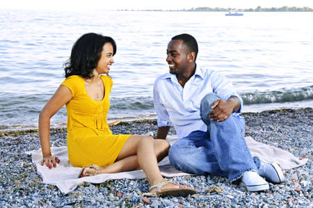 profile: Young romantic couple looking at each other sitting on beach
