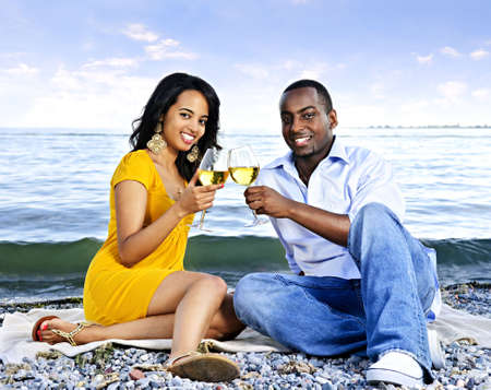 Young romantic couple celebrating with wine at the beach photo
