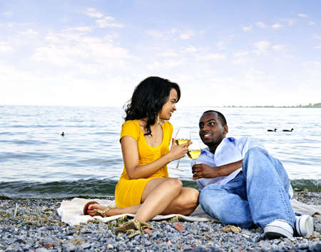 minority couple: Young romantic couple celebrating with wine at the beach looking at each other
