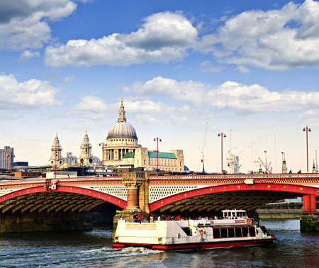 Blackfriars Bridge, St. Pauls Cathedral and cruise boat in London Фото со стока