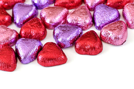 Valentines chocolates wrapped in red and purple foil on white background