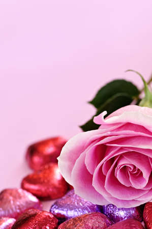Pink rose with Valentine's chocolates wrapped in red and purple foil Stock Photo - 5660965