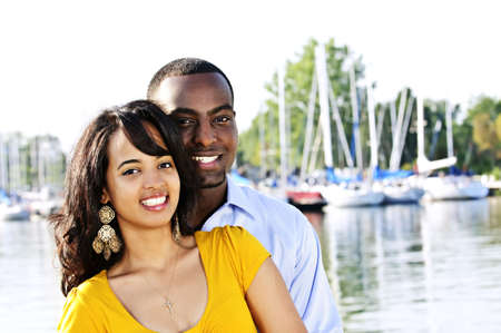 Portrait of young romantic couple standing at harbor photo