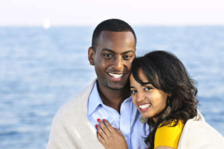 minority couple: Young romantic sharing a blanket by the ocean