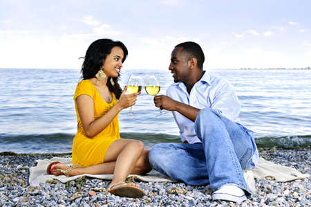 man drinking water: Young romantic couple celebrating with wine at the beach looking at each other