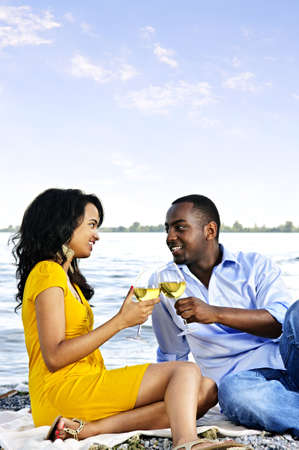Young romantic couple celebrating with wine at the beach with copyspace photo
